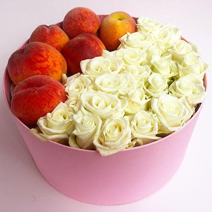 Baltas rozes ar persikiem vai mandarīniem apaļā dāvanu kastē