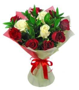 Sarkanas un baltas rozes iepakojumā ar zaļumiem