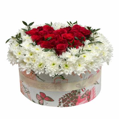 Apaļa dāvanu kaste ar baltām krizantēmām un sarkanām rozēm sirds formā